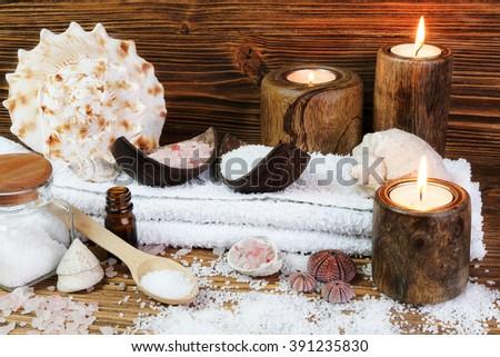 Concept spa with sea saltl and candles on the wooden background
