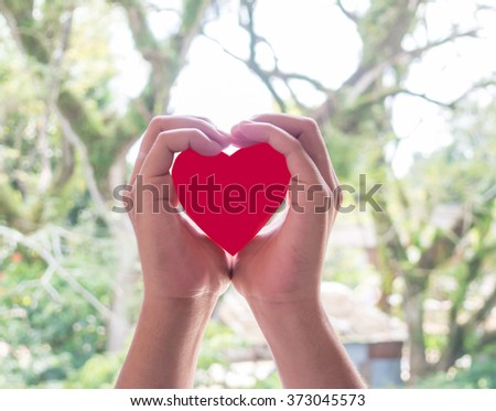 Concept style picture of two hand that hold the heart origami