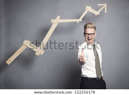 Concept: Success in business. Confident young businessman holding thumb up in front of ascending business graph, isolated on grey background. - stock photo