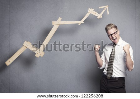 Concept: Successful business. Energetic young businessman cheering in front of ascending business graph, isolated on grey background. - stock photo