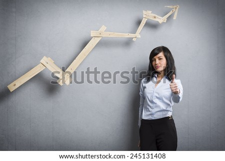 Concept: Successful career or business. Young confident businesswoman holding thumb up in front of ascending business graph, isolated on grey background. - stock photo