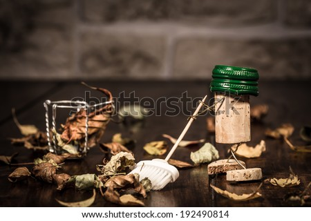 Concept sweep leaves with a broom, wine cork figures - stock photo