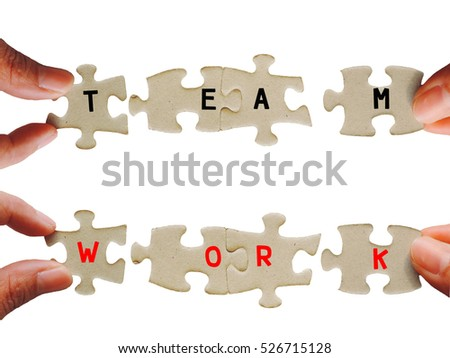 "Concept teamwork in business to success,Hand holding puzzle piece with words""TEAMWORK"" isolated on white background."