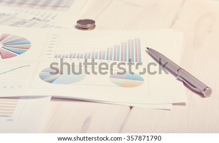 Concept -  toned background picture about work in the office. Business documents close up. Market graphs and charts. Sales plans. Desk in office. Documents, money reports. Office life. - stock photo