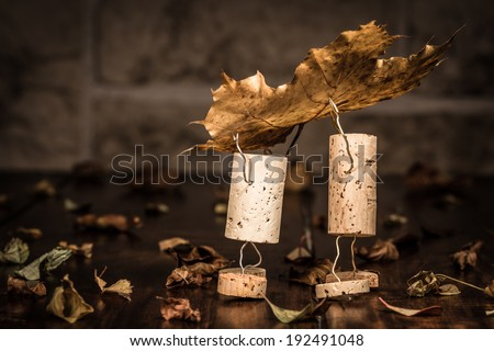 Concept two men carry leaves, wine cork figures - stock photo