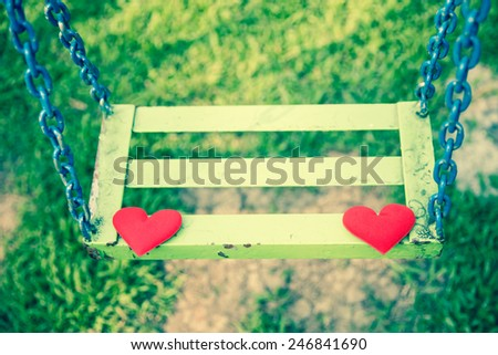 Concept two red valentine hearts on empty chain swing. Retro filter - stock photo