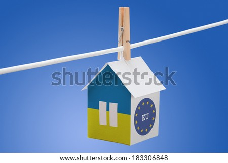 concept - Ukraine, Ukrainian and European Union flag painted on a paper house hanging on a rope - stock photo