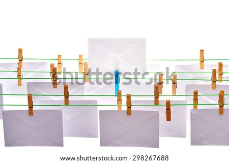 Concept: unique and distinct - many envelopes hanging from wires except for one standing upright - stock photo
