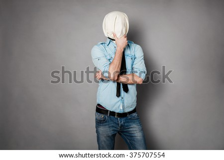 concept with a young man with face covered by a textile material acting normal but having no face, on grey - stock photo