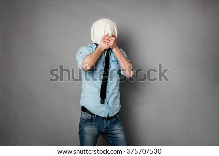 concept with a young man with face covered by a textile material covering his mouth - stock photo