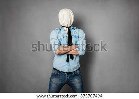concept with a young man with face covered by a textile material crossing his arms, on grey - stock photo