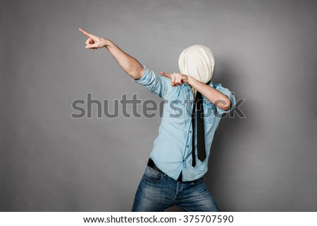 concept with a young man with face covered by a textile material pointing - stock photo