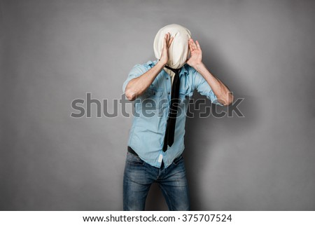 concept with a young man with face covered by a textile material, shouting gesture - stock photo