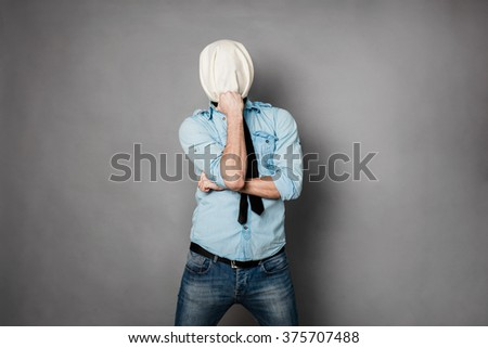 concept with a young man with face covered by a textile material thinking pose - stock photo