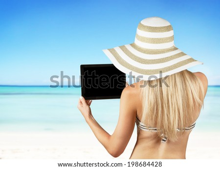 Concept with girl holding tablet in hands, blur tropical sandy beach on background