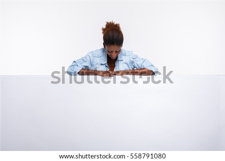 concept with young beautiful black woman leaning on an white empty board dressed in jeans shirt and smiling