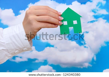 concept: woman hand with paper house on sky background, close up - stock photo