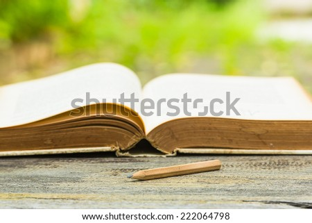 Concept wood pencil on wooden table with old book in garden. - stock photo
