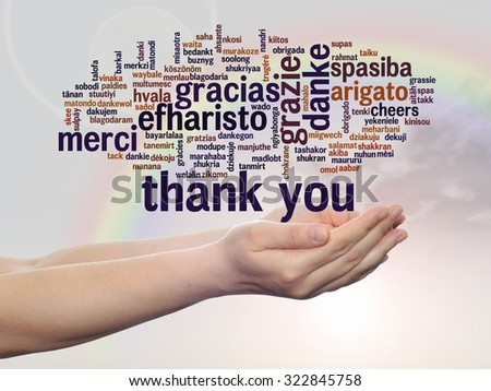 Conceptual abstract thank you word cloud held in hands different language, multilingual as education, thanksgiving day, appreciation, multicultural, friendship, tourism travel over rainbow sky - stock photo