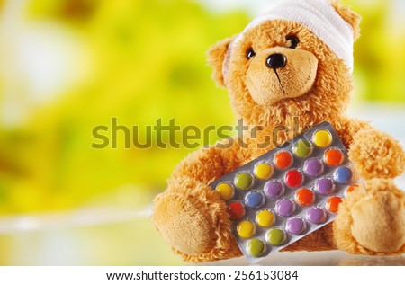 Conceptual Bandaged Brown Plush Teddy Bear with Foil Packaged Colored Pills - stock photo