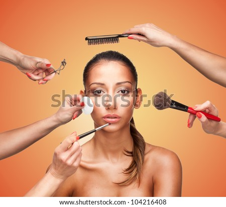 Conceptual beauty and fashion image of the hands of several beauticians and stylists holding their respective equipment giving a glamour makeover to a beautiful woman - stock photo