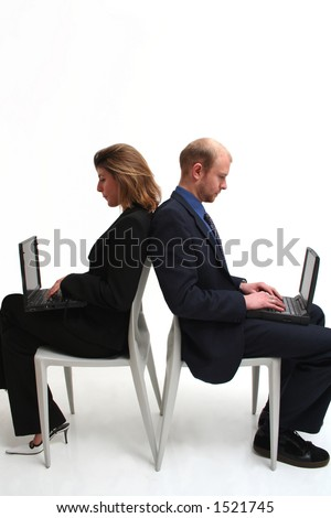 Conceptual business communication, two business people sitting opposite each other useing laptops