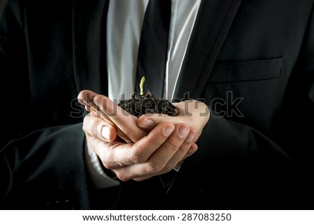 Conceptual Businessman in Black Suit, Holding a Conceptual Soil with Fresh Young Sprout with his both Hands.