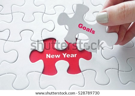 Conceptual: Close up of girl's hand placing the last jigsaw puzzle piece with word New Year Goals