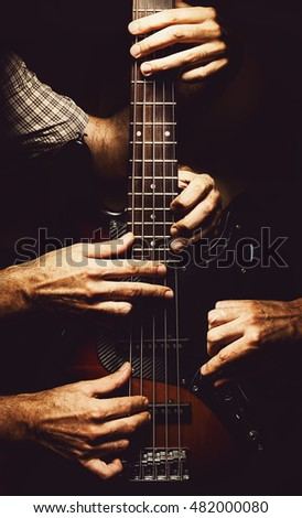 Conceptual composition about playing a modern jazz bass guitar, multiple hands on an instrument.
