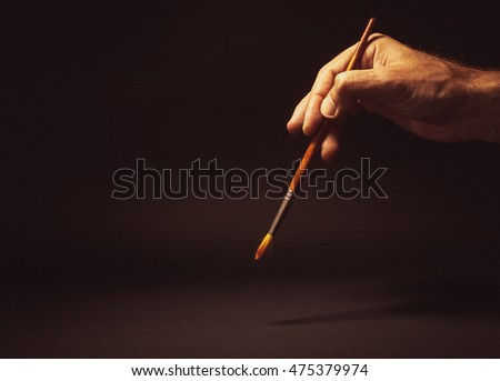 Conceptual composition, man's hand holding a brush on black background.
