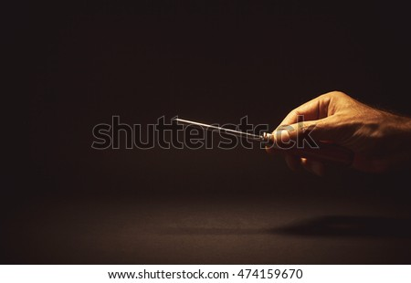 Conceptual composition, man's hand holding a screwdriver.