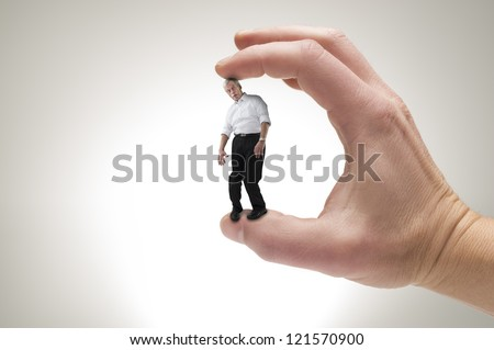 Conceptual creative shot of a man between fingers. - stock photo