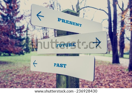 Conceptual Design of Present, Future and Past on Direction Sign Board on a Grassy Landscape with Trees at the Background. - stock photo
