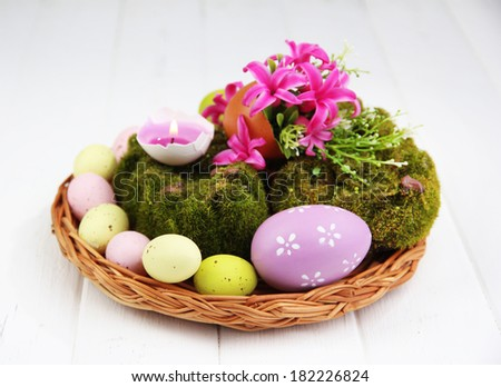 Conceptual Easter composition. Burning candle in egg, Easter eggs,  and flowers on decorative moss and wicker mat, on wooden background, close-up