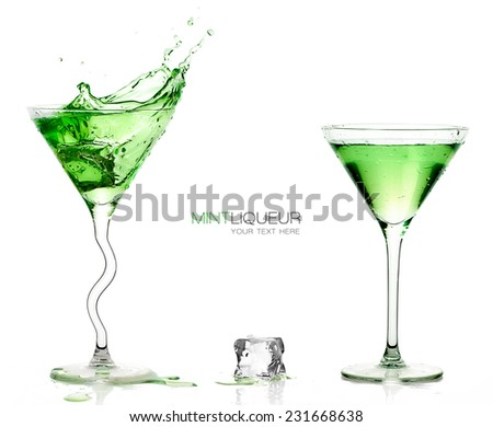 Conceptual Elegant Martini Glasses full of Green Cocktails with one splashing out and Ice Cube on the Table. Isolated on White Background. Template design with sample text  at the Center - stock photo