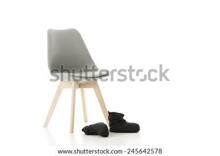 Conceptual Elegant Office Chair and a Pair of Back Shoes Isolated on White Background. Emphasizing Copy Space. - stock photo