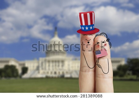Conceptual Family finger art. Couple is celebrating july 4th and holding US flag. Man is wearing a Uncle Sam's hat. Painted fingers creative concept against background of The United States Capitol  - stock photo