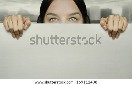 Conceptual girl watching with curiosity over white wall and urban landscape in the background - stock photo