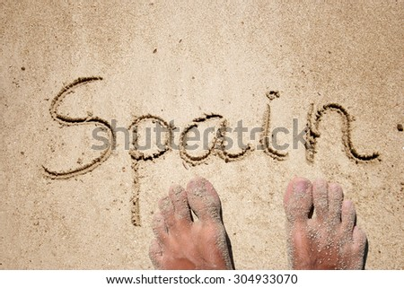 Conceptual hand or handwritten Spain text in sand on beach in exotic island background with feet for summer, ocean, sea, travel, vacation, tourism tropical coast message resort paradise sunny or water - stock photo
