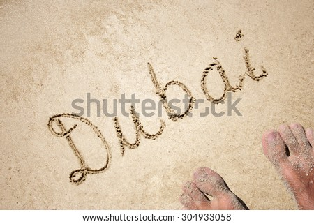 Conceptual  handwritten Dubai text in sand on a beach in an exotic island background with feet for summer ocean sea travel vacation tourism tropical coast message resort paradise sunny or water - stock photo