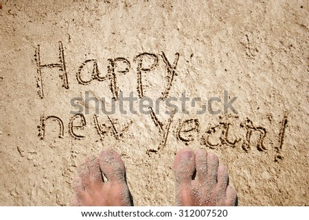 Conceptual handwritten Happy new year text in sand on a beach in an exotic island with feet for holiday, new year, happy, greeting, spring, celebration, travel, vacation, season, tropical or tradition - stock photo