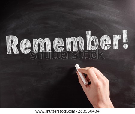 Conceptual Handwritten Remember Text on Black Chalkboard with Hand Holding a Chalk, Captured in Close up. - stock photo