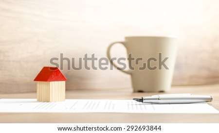 Conceptual Home Miniature, Pen and Contract on Top of the Table with a Cup of Coffee on the Side. - stock photo