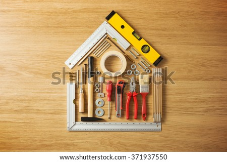 Conceptual house composed of DIY and construction tools on hardwood flooring, top view - stock photo