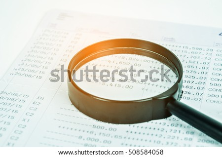 conceptual image analysis of financial statements, documents and magnifier on an office desk