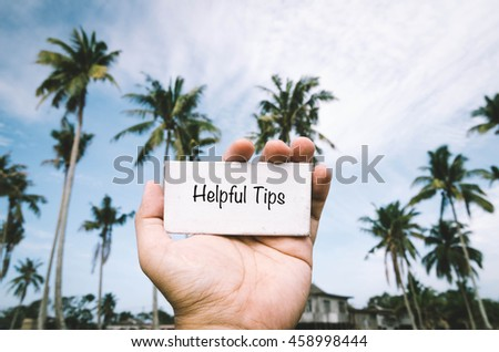 conceptual image, cropped hand holding white frame canvas with word HELPFUL TIPS over blurred village background. color tone applied - stock photo