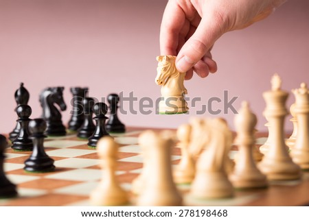 Conceptual image depicting making a strategic move with a hand moving a chess piece on a chessboard during a game of skill - stock photo
