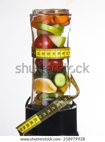 Conceptual image - fresh fruits and vegetables in a mixer with measuring tape on a white background. - stock photo