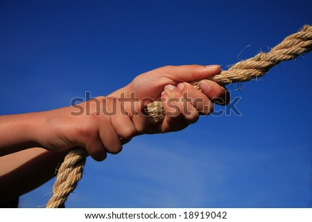 Conceptual image - hands pulling on a rope blue sky background. Might signify strength pulling power determination teamwork etc. - stock photo