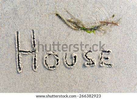 "Conceptual image indicating a beach house by writing the word ""House"" in the sand."